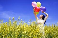 Kvinna som rymmer färgrika ballonger i senapsgult fält på en solig dag arkivbilder