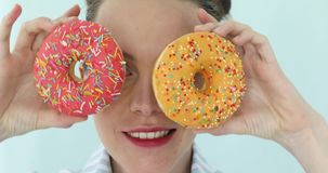 Kvinna som rymmer färgrika rosa donuts mot hennes ögon arkivfilmer