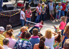 Kvinna som rymmer henne skor och över tillbaka böjer för att dansa under en limbostång som in omges av folk i tropiclkläder på pa Royaltyfria Bilder