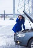 Kvinna som rymmer hennes huvud och tänker om den brutna bilen Arkivfoto