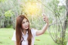 Kvinna som rymmer hennes mobiltelefon och tar selfie royaltyfri foto