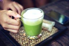 Kvinna som rymmer latte Matcha för grönt te på trätabellen Royaltyfri Fotografi