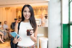 Kvinna som rymmer med is kaffe och mobiltelefonen royaltyfri bild