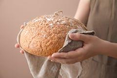 Kvinna som rymmer nytt smakligt bröd på färgbakgrund, closeup royaltyfria foton