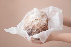 Kvinna som rymmer nytt smakligt bröd på färgbakgrund, closeup arkivbilder