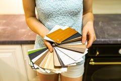 Kvinna som rymmer och visar den färgrika texturmodellen och färgpaletten - provkartor som ska väljas från royaltyfri fotografi