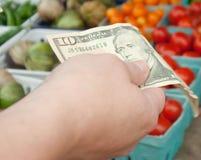 Kvinna som rymmer räkning $10 på marknaden för bonde` s Royaltyfri Fotografi