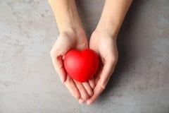 Kvinna som rymmer röd hjärta på den gråa tabellen, bästa sikt cardiology royaltyfri foto
