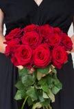 Kvinna som rymmer röda rosor arkivbilder