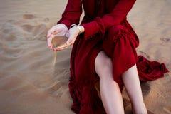 Kvinna som rymmer sand i öknen royaltyfri bild