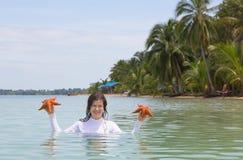 Kvinna som rymmer sjöstjärnan Arkivfoto