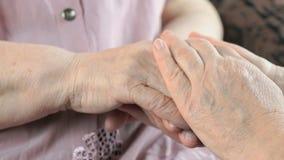 Kvinna som rymmer sladdriga rynkiga händer av den gamla kvinnan lager videofilmer