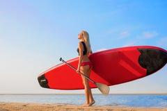 Kvinna som rymmer SUP arkivfoton