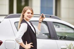 Kvinna som rymmer tangenter till den nya bilautomatiskn och ler p? kameran arkivbild