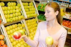 Kvinna som rymmer tre äpplen i händer Royaltyfri Fotografi