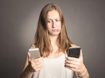 Kvinna som rymmer två cellulars royaltyfria bilder