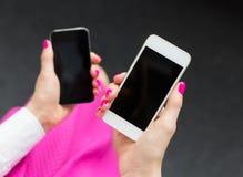 Kvinna som rymmer två mobiltelefoner Arkivbild
