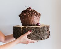 Kvinna som rymmer upp en chokladkaka på en träplatta, slut Läckert bageri och att ge den höga kalorin arkivbild