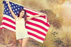 Kvinna som rymmer USA flaggan utomhus- Fotografering för Bildbyråer