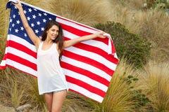 Kvinna som rymmer USA flaggan utomhus- Royaltyfria Foton