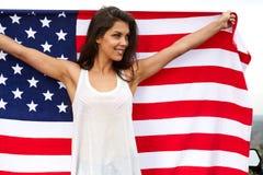 Kvinna som rymmer USA flaggan utomhus- Royaltyfri Foto