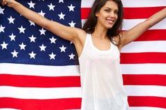 Kvinna som rymmer USA flaggan utomhus- Royaltyfria Bilder
