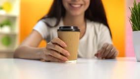 Kvinna som rymmer varmt kaffe i pappersexponeringsglas och ler, morgonenergi, avbrott arkivfoto