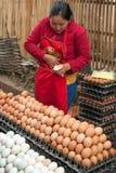 Kvinna som säljer ägg på den traditionella asiatiska matmarknadsplatsen Arkivfoton