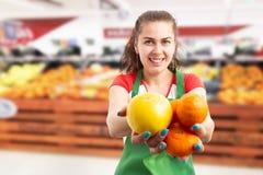 Kvinna som säljer livsmedel som framlägger apelsinen och tangerin royaltyfri fotografi