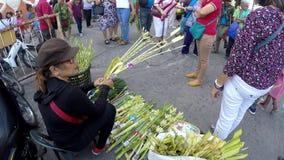 Kvinna som säljer palmblad för att sköta om palmsöndagberöm