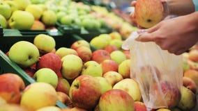 Kvinna som sätter äpplet till påsen på livsmedelsbutiken stock video