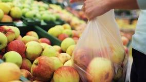 Kvinna som sätter äpplet till påsen på livsmedelsbutiken lager videofilmer