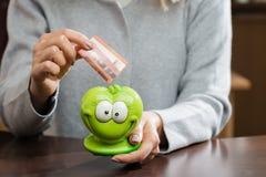 Kvinna som sätter affärskortet i en rolig grön moneybox Begreppsnolla Royaltyfria Bilder