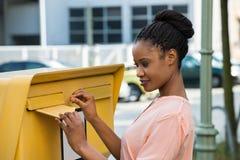 Kvinna som sätter in bokstaven i brevlåda royaltyfria foton