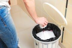 Kvinna som sätter den tomma plastpåsen i återvinningfack i köket Royaltyfri Bild
