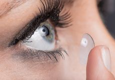 Kvinna som sätter in en kontaktlins Arkivfoto