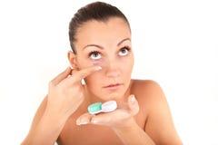 Kvinna som sätter in en kontaktlins i hennes öga Royaltyfria Bilder