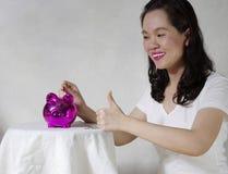 Kvinna som sätter en mynta in i sparbössan Royaltyfri Foto