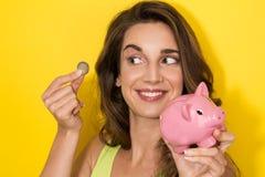 Kvinna som sätter ett mynt i den lilla spargrisen royaltyfri fotografi