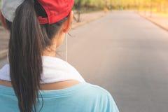 Kvinna som sätter hörlurar för att lyssna musik Hon som joggar i det offentligt, parkerar med solljus i bakgrunden royaltyfri fotografi