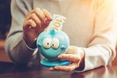 Kvinna som sätter hundra eurosedel i en rolig blå moneybox Arkivbilder