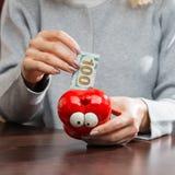 Kvinna som sätter hundra eurosedel i en rolig röd moneybox Royaltyfri Foto