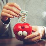 Kvinna som sätter hundra eurosedel i en rolig röd moneybox, Royaltyfria Bilder