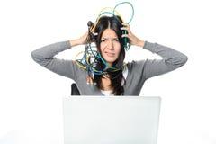 Kvinna som sätter kablar på huvudet, medan genom att använda bärbara datorn Royaltyfri Fotografi