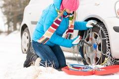 Kvinna som sätter kedjor på bilvintergummihjul royaltyfria foton