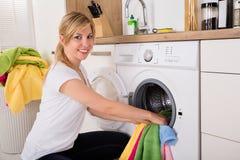 Kvinna som sätter in kläder i tvagningmaskin royaltyfri foto