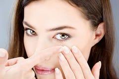 Kvinna som sätter kontaktlinsen Arkivbild