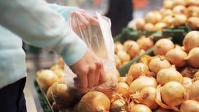 Kvinna som sätter löken till påsen på livsmedelsbutiken stock video