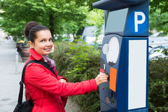 Kvinna som sätter in myntet i parkeringsmeter royaltyfri fotografi