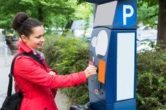 Kvinna som sätter in myntet i parkeringsmeter arkivfoton